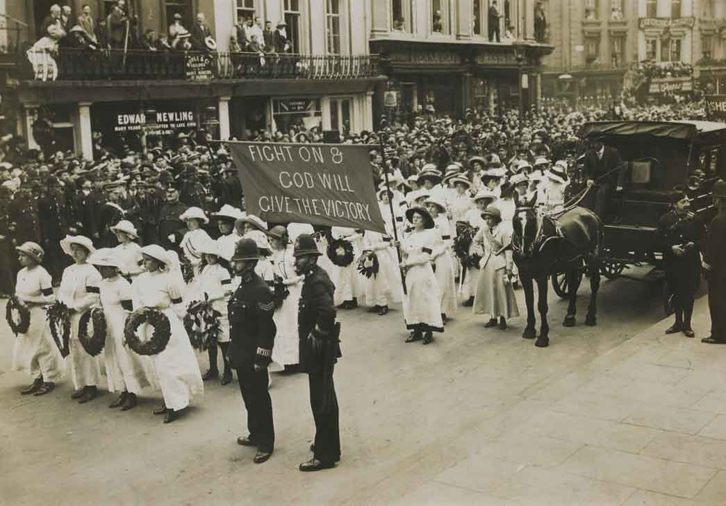 The funeral of Emily Wilding Davison, 14 June 1913. The image depicts one of the banners carriers in the procession bearing the defiant message 'Fight on & God will give the Victory' This banner in purple fabric preceded the long sections of London members of the Women's Social and Political Union. Ahead of the banner are Suffragettes carrying laurel wreaths. Suffragettes taking part in the procession were required to wear either white, purple, scarlet or black according to their role and position in the procession. As white succeeded purple and scarlet black the the resulting spectacular effect resembled, as noted the Manchester Guardian, 'the long unfurling of a military banner'.