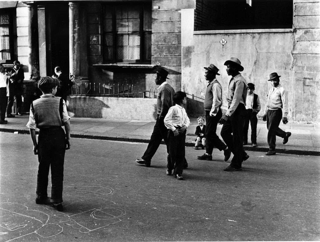 Roger Mayne, A group of black men walking along Southam Street, W10, 1956