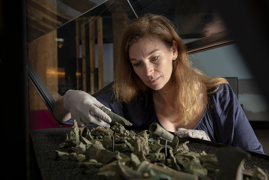Bronze Age objects including an axe head being installed by Curator Kate Sumnall (c) Museum of London.jpg
