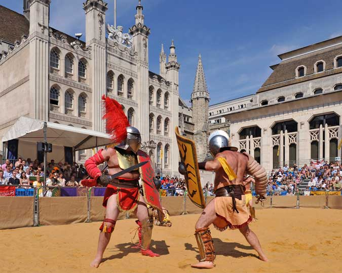 Two Roman-style gladiators fight outside the Guildhall.