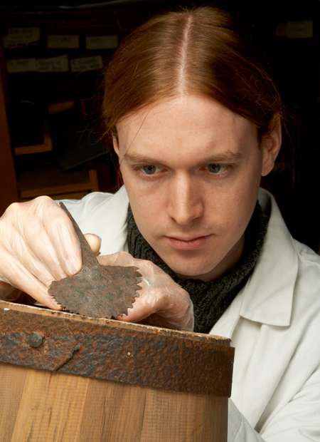 Archaeologist Owen Humphries holds a Roman tool known as a croze, used in barrel-making.