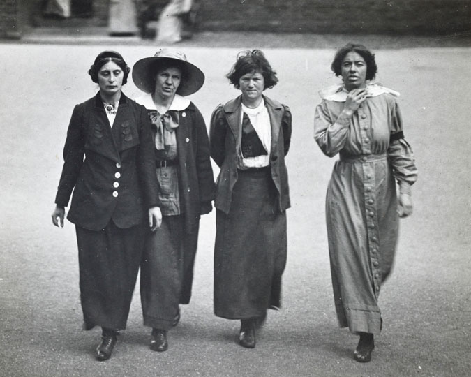 Surveillance photograph of four suffragette prisoners exercising in the yard of Holloway jail. The prisoners are identified on the reverse of the photo as Margaret Scott, Jane Short, May McFarlane & Olive Hockin. The image was taken by an undercover photographer on orders from the Home Office.
