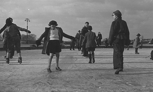 Skaters on Whitestone Pond, Hampstead Heath in January 1954. Whitestone pond (originally known as Horse Pond) was originally a small dew pond, which was enlarged and filled with water to provide refreshment for military horses in 1890. The pond is located at the one of the highest points in London. As can be seen in the photograph you didn't need a proper pair of skates to enjoy the icy conditions of the pond, many people slipped and slid in their shoes.
