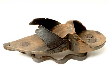 Woman or girl's patten with wooden sole and two black leather straps with holes for ties across the feet. This patten has an undulating curved metal ring under the sole to raise the patten above ground. The toe is pointed and reinforced with metal from the patten ring. This patten has no heel but has a heel socket which measures 2.8 cm. It has a straight sole so it could be worn outdoors. The leather straps are nailed on with three nails and are reinforced. There is a wavy iron ring nailed on at the forepart and two nails at the heel.