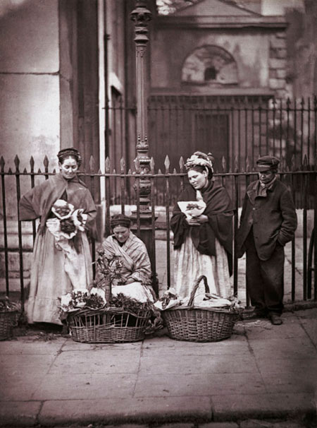 Covent Garden flower women, c. 1877. This group of flower sellers are standing outside St. Paul's Church, their regular spot through generations. Whilst Covent Garden Flower, Fruit and Vegetable Market was a wholesale market, there was room for a few sellers of nosegays to passers-by. Poignantly, Adolphe Smith contrasts the life of these Covent Garden flower sellers with that of Isabelle, the favourite flower-girl of the Paris Jockey Club, who was well rewarded for her services. From a series of 37 photographs published in the book, 'Street Life in London' (1877), with text written by Thomson and the journalist Adolphe Smith. [p.8]