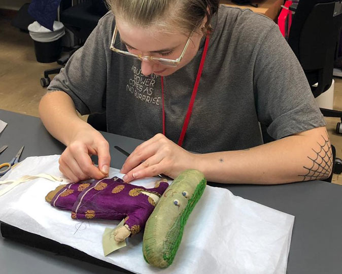 Conservation student Echo Godfrey-Simson stitches a vegetable doll, Lord Cucumber.