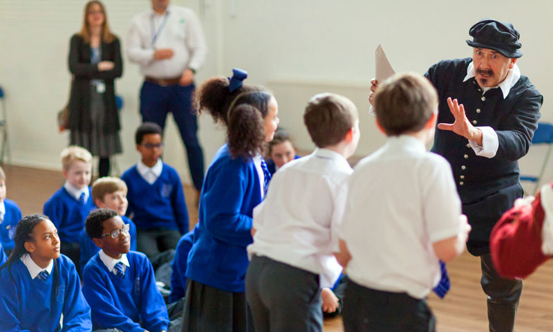 An actor in a school hall during a performance of an 'at your school' show.