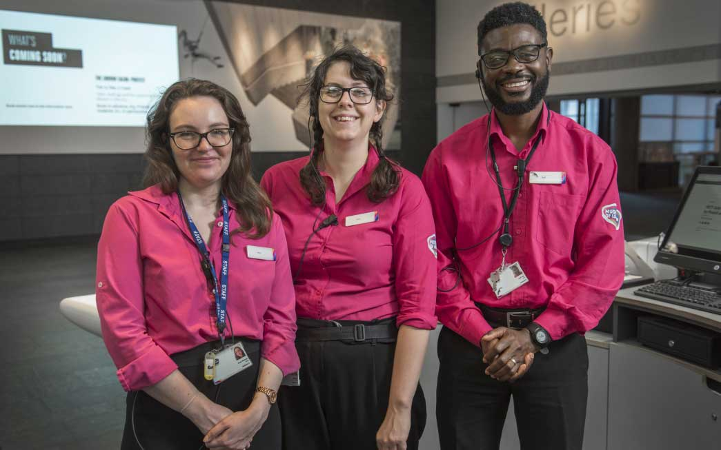 Three members of our Visitor Experience team smile in the foyer of the Museum of London.
