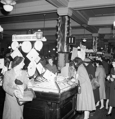 Interior of Selfridges, next to embroidery sets for sale. Women customers sorting through the goods. Christmas 1953