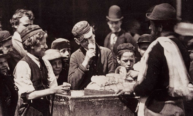 Children gather round the barrow of an ice cream seller, c. 1877.