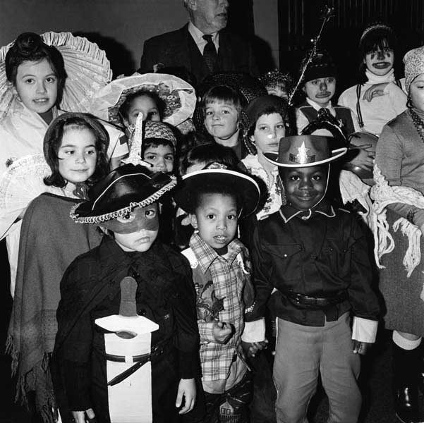 A black and white photo of a group of children in different fancy dress costumes at a party.