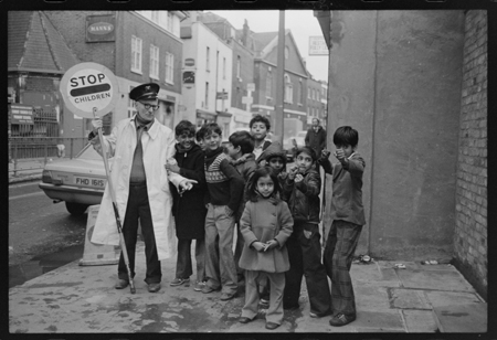 A male crossing patrol warden stands by a group of Asian children outside Christchurch Church of England School, in Spitalfields, 1979.
