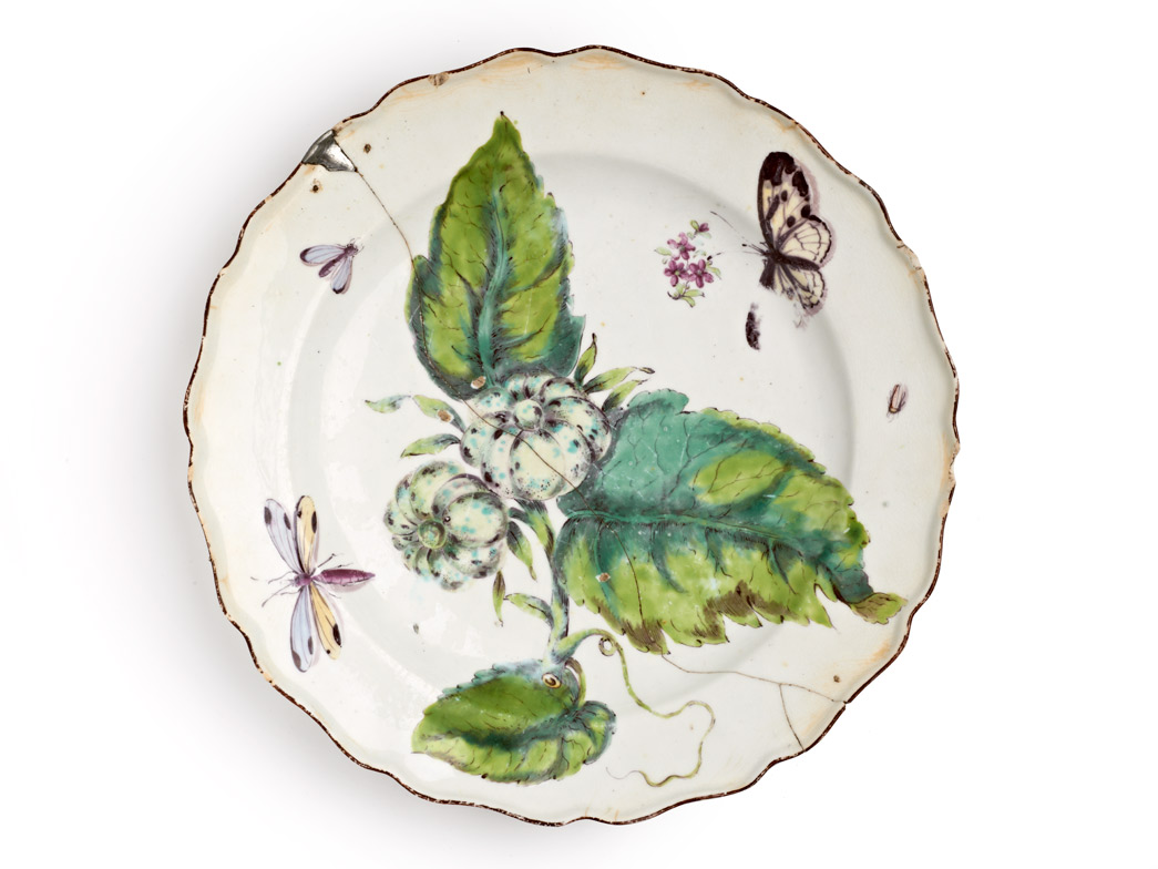 Plate, decorated in 'Hans Sloane' botanical style with enamelled flowers, ladybird, dragonfly and a chocolate line rim. Marked on the base with an iron red anchor over '15', and repaired with rivets.