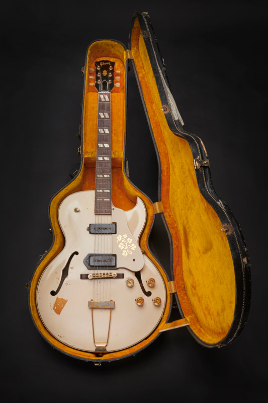 A 1950S GIBSON ES-295 with a white finish inside a hardshell contour case with orange plush lining. The guitar was used by Mick Jones during recording of the London Calling album and in the music video for the title track of the album, released as a single in December 1979.