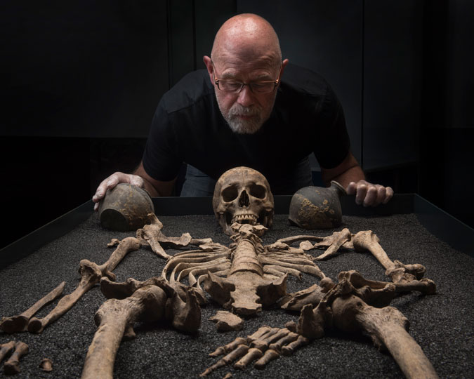 Cliff Thomas installs a skeleton in the Roman Dead exhibition at the Museum of London.