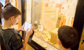 A child looks into a display case and uses their phone during a supplementary school session.