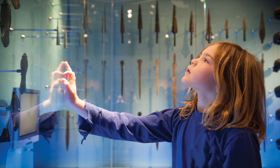 girl looking at blue display, with her hand on the glass