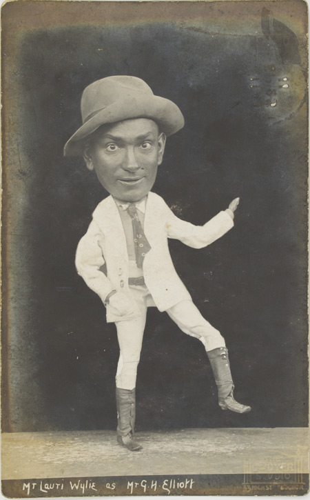 Postcard showing a performer with a doll hanging from his head.