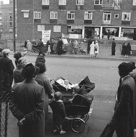 Kennistoun House rent protest, Kentish Town. Local people gather outside Kennistoun House, Kentish Town, to watch an angry protest over rent and to prevent a police van from entering the courtyard. Tenant Don Cooke, who had barricaded himself in his council flat, had been evicted from the house that morning. He and fellow tenant Arthur Rowe were protesting against rent increases demanded by St Pancras Borough Council. Henry Grant.