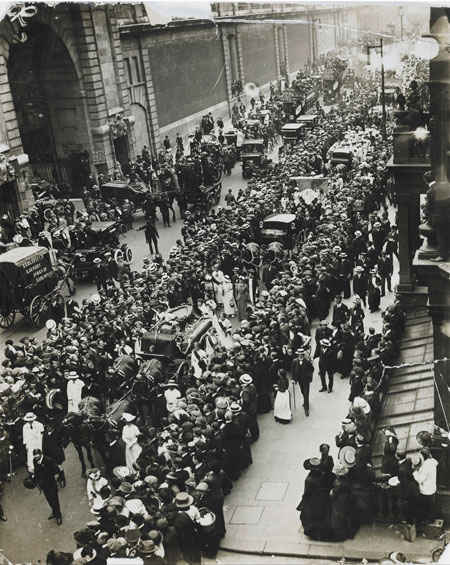 An aerial view of the funeral procession of Emily Wilding Davison approaching Victoria on the 14 June 1913. On 4 June 1913 the suffragette ran onto the Derby race course in an attempt to stop the King's horse. Seriously injured, she never regained consciousness and died four days later. The funeral procession, organized by Grace Roe, made its way in London to St. George's, Hart Street (now New Oxford Street) and Bloomsbury. After a funeral service at St George's, Bloomsbury, the coffin was transported to King's Cross station and on by train to the Davison family home of Morpeth, Northumberland.