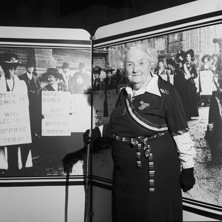 Former suffragette, Connie Lewcock. A government exhibition was staged inside Westminster Hall to mark the 50th anniversary of women's right to vote. Connie Lewcock O.B.E, an 84-year-old former suffragette from Newcastle, attended the private view, she is wearing some original suffragette movement insignia. Lewcock had helped to set fire to Esh Winning railway station in the name of suffrage. The exhibition, which included material from the Museum of London, opened with speeches from Prime Minister James Callahan, opposition leader Margaret Thatcher and Liberal Dame Margaret Corbett-Ashby.