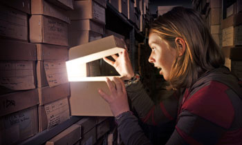A young woman explores the archive and finds new treasures. (c) Museum of London, Picturechase no 009553.