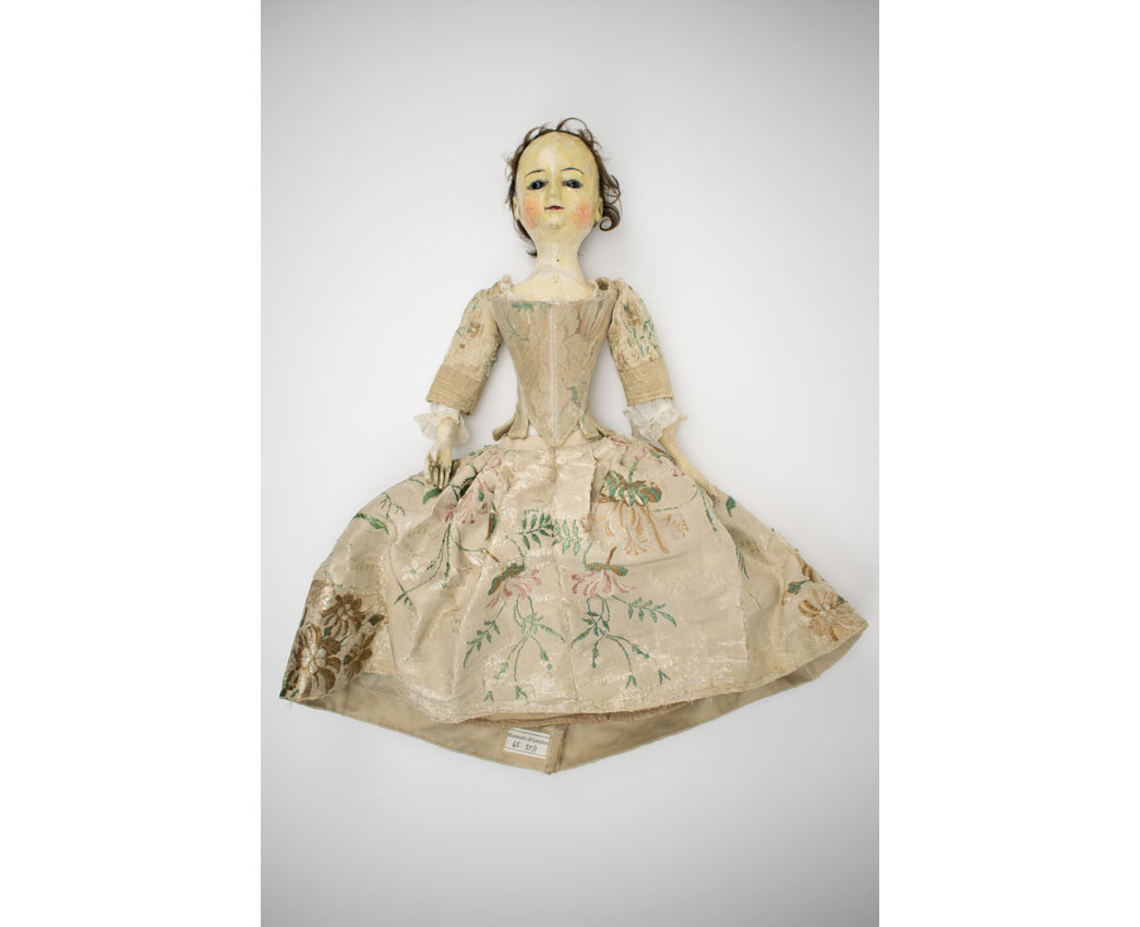 This is one of the older dolls in the collection, dating from around 1750-1760. Her dress is a fashionable style typical of the period, made from fine floral-patterned silk woven in England.