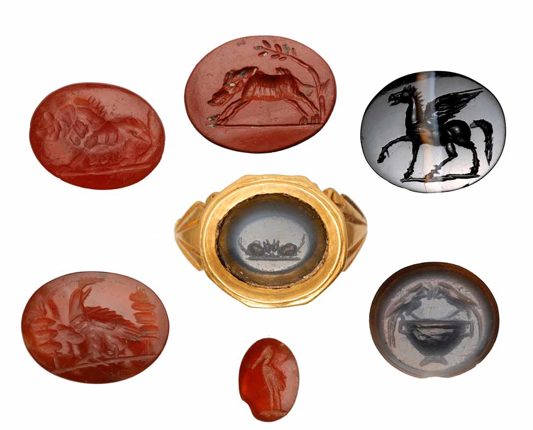 Selection of Roman intaglios. This group of roman intaglios showcases a variety of decorative motifs including animals, clasped hands and birds. Some of these intaglios were used as decoration for finger rings. The engravings on them are varied among them there are representations of animals, like the lion on the top left which could represent the sign of the zodiac Leo or be a symbol of strength worn to ward off the evil eye. In this instance, however, the lion more likely symbolises the devouring power of death. The intaglio on the centre left depicts a military eagle set between two legionary standards. The other engravings show a pair of clasped hands, the winged God Pegasus, two mice and parrots.