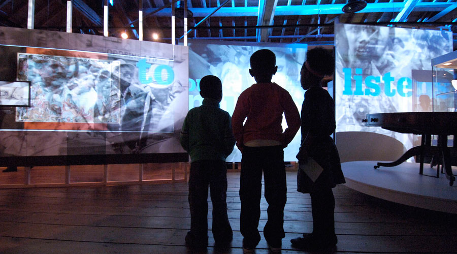 Primary pupils stand in front of a display about slavery on a visit to the  Museum of London Docklands