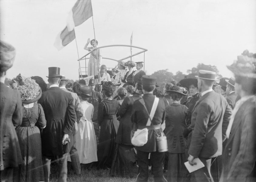 A Suffragette speaker in Hyde Park, Women's Sunday, 21st June 1908. Women's Sunday was the first 'monster' meeting to be organised by the militant Women's Social and Political Union. Specially chartered trains transported thousands of Suffragettes from all over Britain to march in seven processions through central London to a rally in Hyde Park. The highly choreographed demonstration attracted a crowd of up to 300,000 drawn by the colourful spectacle of the delegates dressed in the suffragette tricolour and carrying over seven hundred embroidered banners. 'Never', reported the Daily Chronicle, has so vast a throng gathered in London to witness a parade of political forces'.