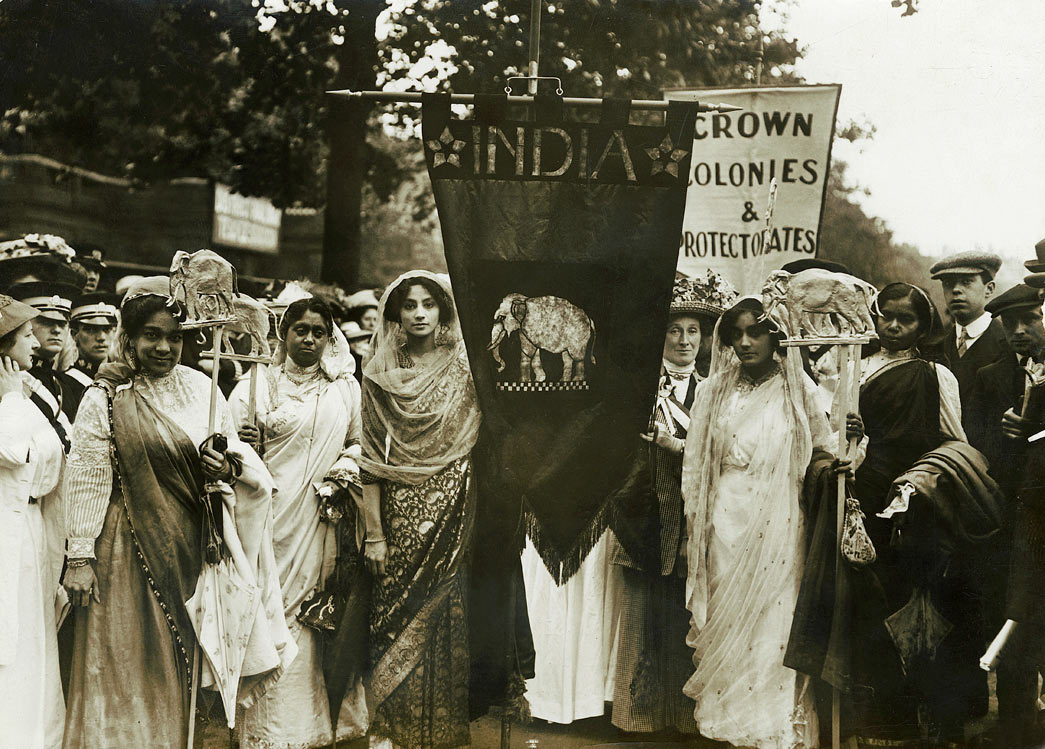 Indian suffragettes on the Women's Coronation Procession of 17 June 1911. The small Indian contingent was organised by Mrs Jane Fisher Unwin (the daughter of Richard Cobden). She and other representatives of the WSPU contacted Indian women living in the UK in the weeks leading up to the procession, organised the decorations and the collection of subscriptions for the elephant banner that cost between £4 & £5. The India procession was part of the 'Imperial Contingent' and intended to show the strength of support for women's suffrage throughout the Empire. On the far left of the image can be seen Lolita Roy who had moved from India to Hammersmith, London with her children in 1901. Lolita, a supporter of female suffrage in India became President of the London Indian Union Society. It is possible the young women also seen in the image were Lolita's daughters.