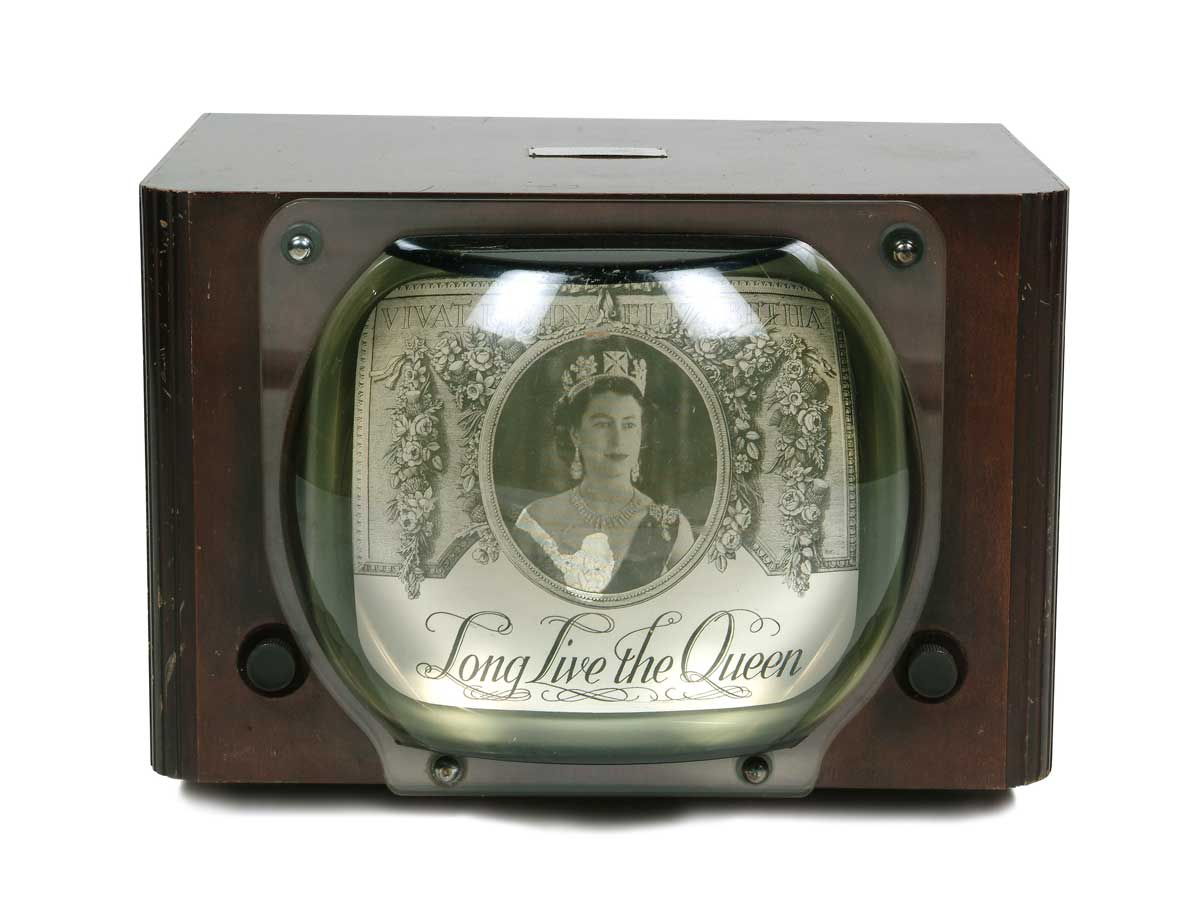 Pye television set in wooden case with paraffin filled magnifier. This television set has the portrait of Queen Elizabeth. Early television sets were installed in wooden cabinets. Tabletop models first emerged in the 1940s a result of the shortage of wood in post-war Britain.