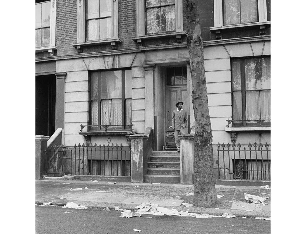 A man on the doorstop of terraced house, Kensington.