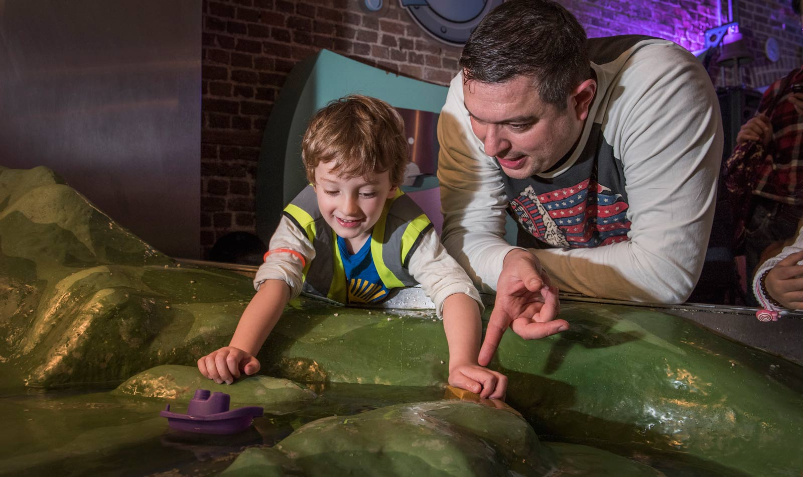 A child and his father play in the Foreshore Find play area of the Mudlarks gallery.