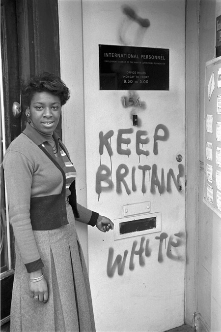 A woman stands outside the door of the Employment Agency of the Martin Luther King Jr. Foundation which has been vandalised and marked 'KEEP BRITAIN WHITE'. As she gestures towards the graffiti, the woman gazes out towards the photographer.