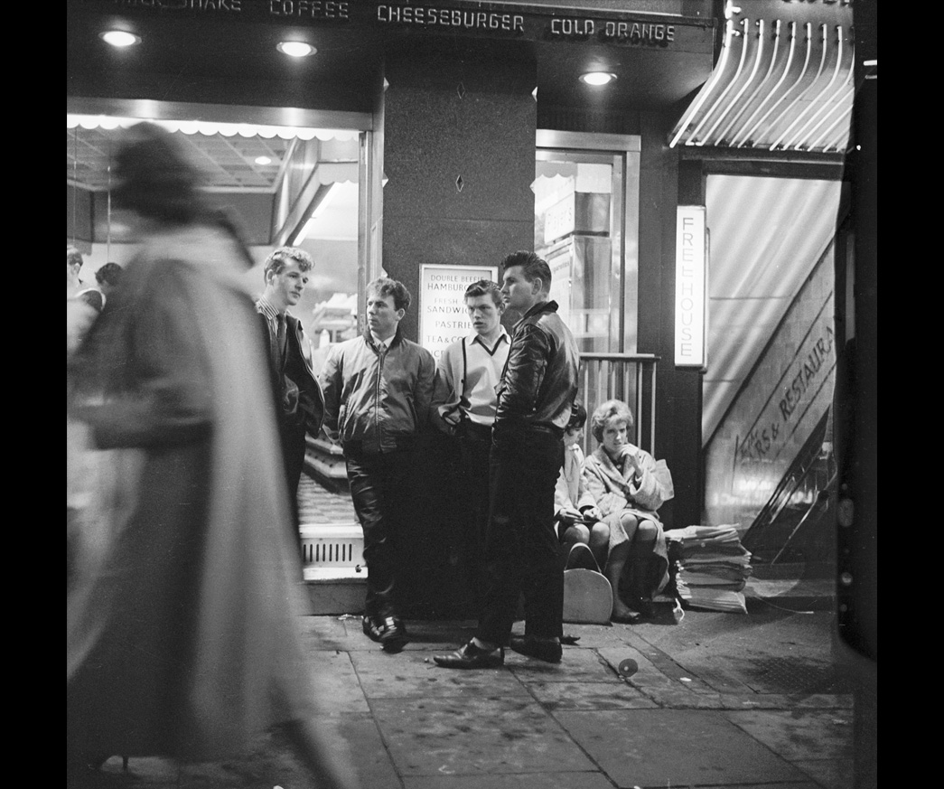 A group of 'teddy boys' outside a burger bar; 1962. Photograph by Henry Grant. Film should include credit © Henry Grant Collection/Museum of London