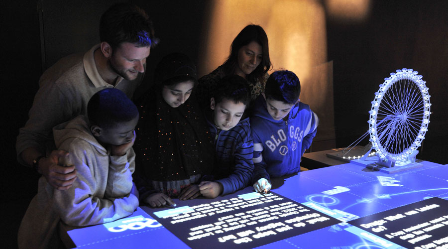 A family uses the interactive projected river in the World City gallery