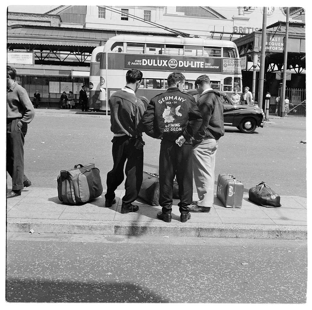 Group of young men wearing bomber jackets at a bus stop.