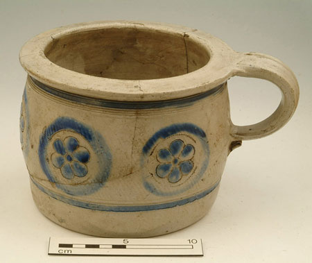 Westerwald stoneware chamber pot (type 2) with incised rings, and flowers with incised outline and painted blue. Found 1929, from bottom of old cess pool, site of public baths.