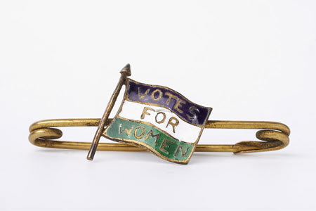 Suffragette bar brooch with gilt metal fastening and central decoration of a purple white and green enamel flag marked 'Votes for Women'.