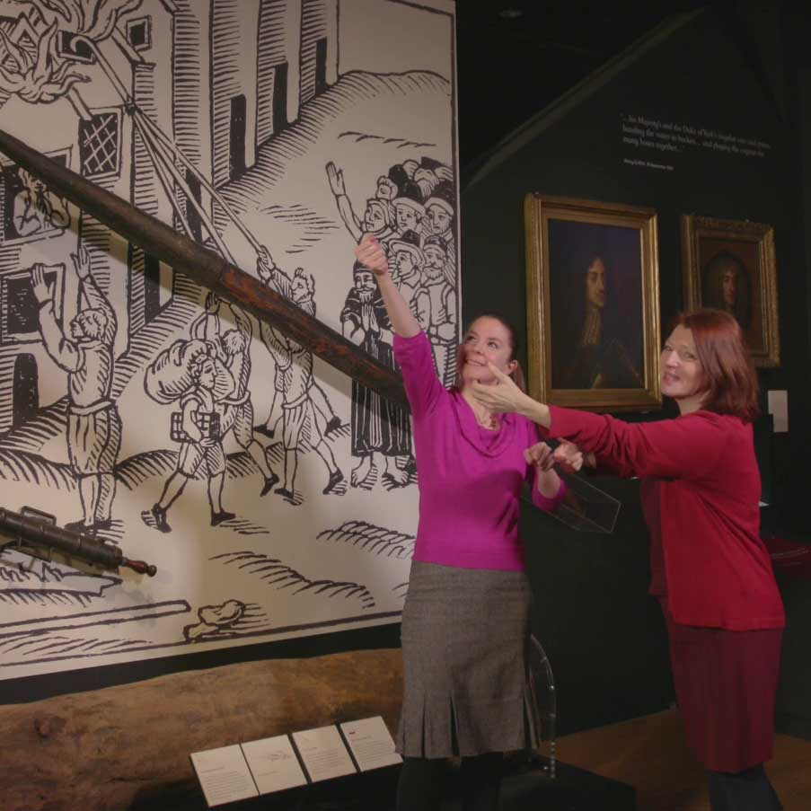 Meriel and Nina pretend to use a fire hook next to a large replica and illustration of the fire.