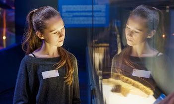 A girl viewing an object during a supplementary schools visit to the Museum of London.