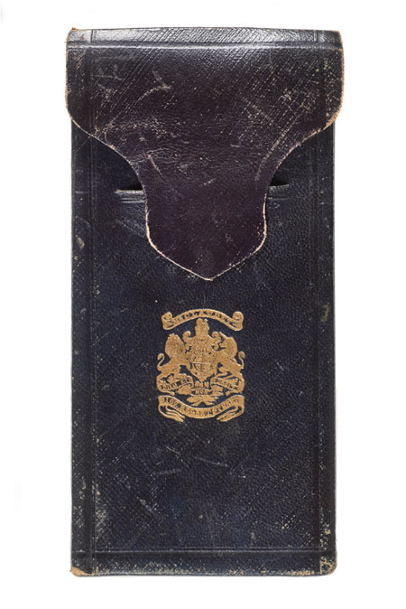 Bookshaped, expanding case of dark blue leather. Decorated with gilt. Brass clasp. Opens to reveal two daguerreotypes and pair of binoculars. Case lined with purple velvet. Leather spine broken. One picture speckled with black.