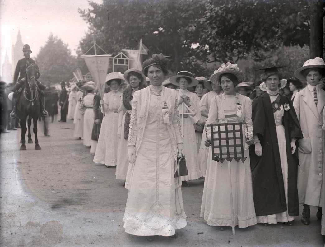 Suffragette prisoners prepare to take part in a procession In support of the Conciliation Bill, 23rd July 1910. In the foreground are the leading Suffragettes Emmeline Pethick-Lawrence on the left and Sylvia Pankhurst holding a model of prison gates. To the right in her graduation robes is Emily Wilding Davison. This procession was organised by the Women's Social and Political Union to take place on the anniversary of the day in 1867 when men demonstrating for their inclusion in the Reform Bill pulled down the railings in Hyde Park. Two processions, one from the west and one from the east converged on Hyde Park where 150 speakers addressed at crowd of up to 20,000 from 40 platforms.