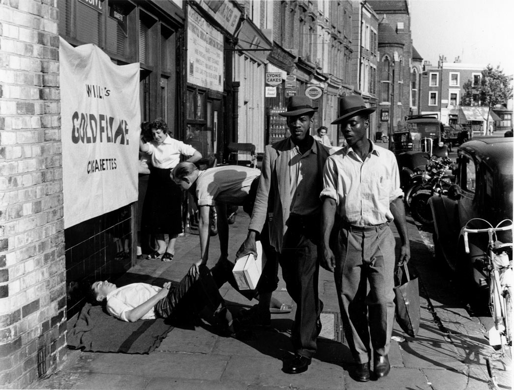 Two black men pass by a man lying on the pavement with another man standing over him and a woman watching, Latimer Road area, North Kensington, 1957.