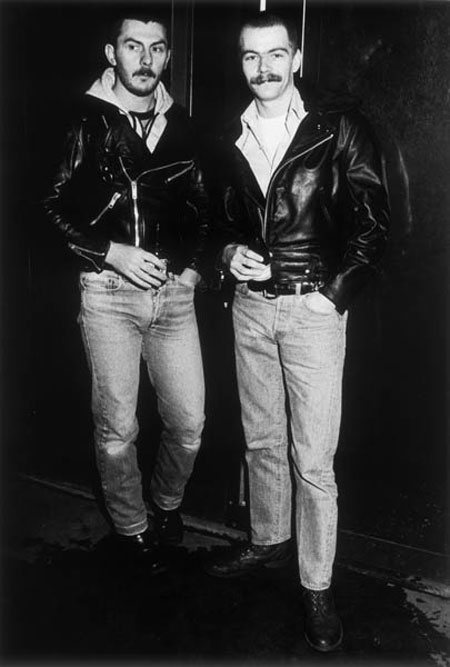 Two young gay men sporting moustaches and black leather jackets posing for the camera outside a pub or club, 1985.