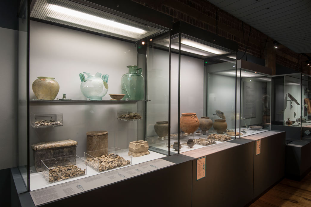 Glass cremation vessels on display in Roman Dead.