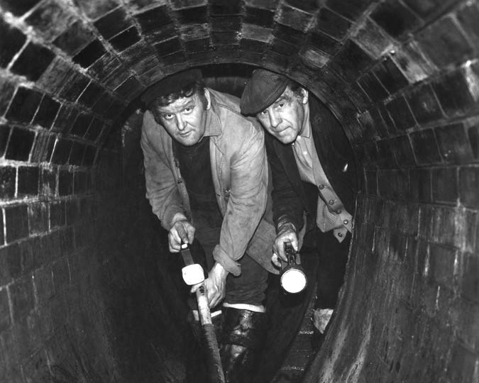 Two men in a Victorian brick-lined sewer photographed in the 1960s.