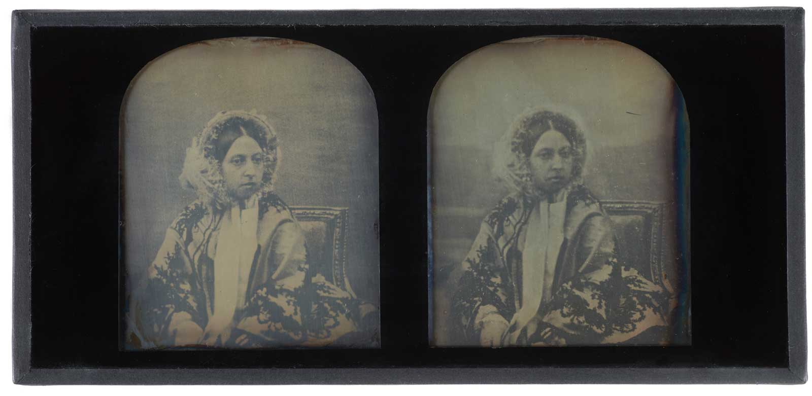 Hand-tinted stereoscopic daguerreotype of Queen Victoria, c. 1850, by Antoine Claudet.  Bookshaped, expanding case of dark blue leather. Decorated with gilt. Brass clasp. Opens to reveal two daguerreotypes and pair of binoculars. Case lined with purple velvet. Leather spine broken. One picture speckled with black.