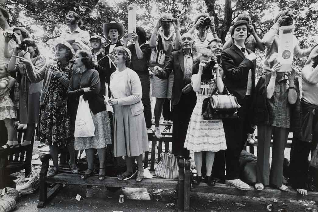 Photograph of the onlooking crowd stood on benches watching events on the wedding day of Prince Charles and Lady Diana Spencer, July 29th 1981.
